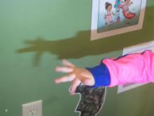 A child uses her hand to make shadow puppets on the wall.