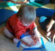 Baby enjoying sensory activity of painting.
