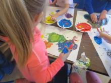 A preschool girl finger painting.