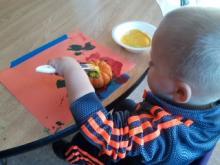 Toddler painting a mini-pumpkin
